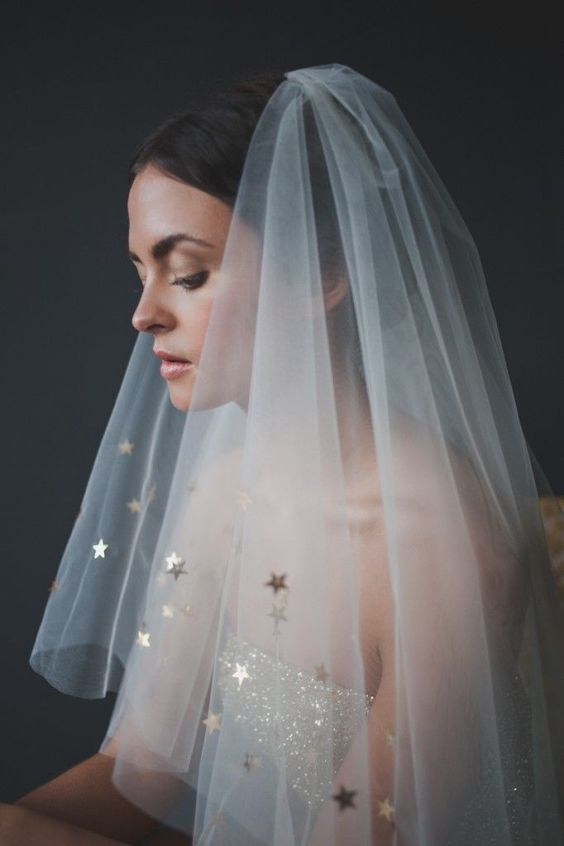 a bride wearing a star veil and a shiny strapless wedding dress for a celestial wedding