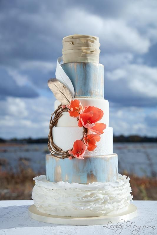 a bright boho wedding cake in blue, white, gold, with tiered and textural layers, with an edible wreath with feathers and blooms