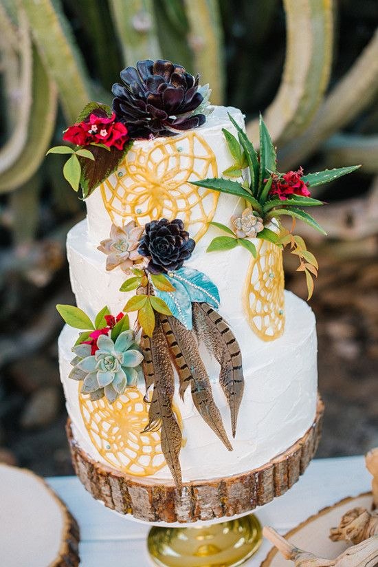 a bright boho wedding cake with painted dream catchers, sucuclents, bright blooms, succulents and feathers