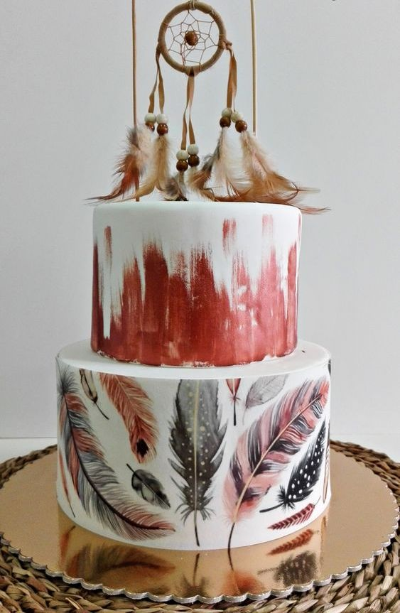 a bright boho wedding cake with painted feather and bustroke tiers, with a dream catcher with beads and feathers