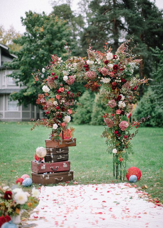 a bright fall wedding arch with a stack of suitcases and globes around for a travel-themed wedding
