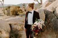 a burgundy tux, a black bow tie and suspenders, tan booties and a man bun to add a casual feel to a formal look