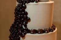 a buttercream wedding cake topped with edible coffee beans and with coffee mugs on top is a fun idea