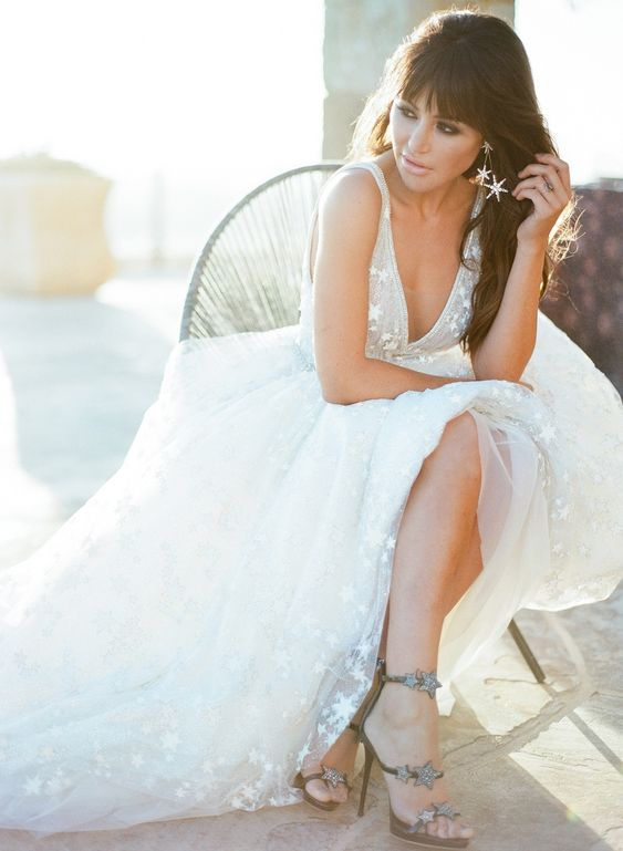a celestial bride wearing a star A-line wedding dress with a deep neckline and no sleeves, star heels and earrings