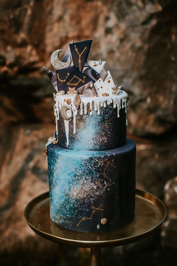 a celestial wedding cake done in navy, with turquoise and golds, with chocolate shards on top and some stars and a moon