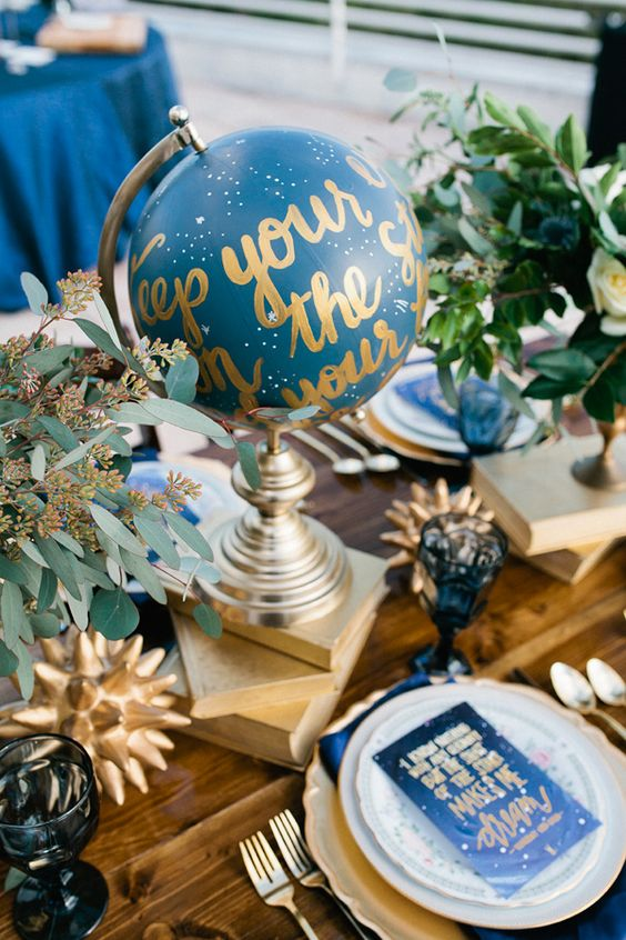 a celestial wedding table with a blue and gold globe, greenery, books, blue glasses and gold cutlery