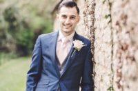 a chic barn groom's look with a navy suit, a checked waistcoat, a creamy tie and button down