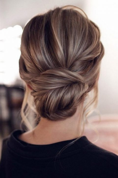 a chic fishtail braid low un with a messy volume on top and some locks down is amazing