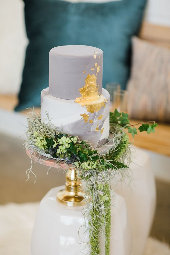 a chic grey and white wedding cake with a marble tier, gold leaf and lots of greenery, blooms and thistles
