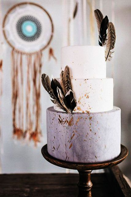 a chic lilac marble and white wedding cake with gold leaf and feathers is a nice idea for a boho wedding