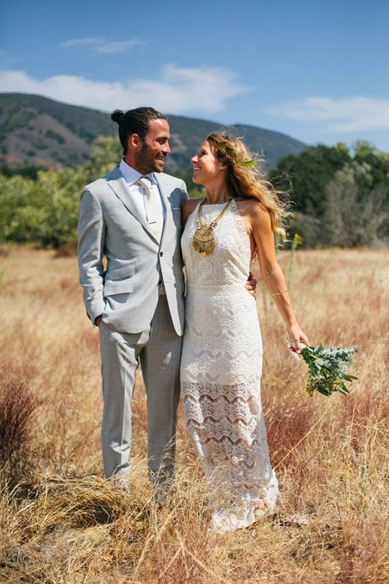 a chic summer groom look with a light grey suit, a wihite shirt and a tie, a man bun is boho and cool