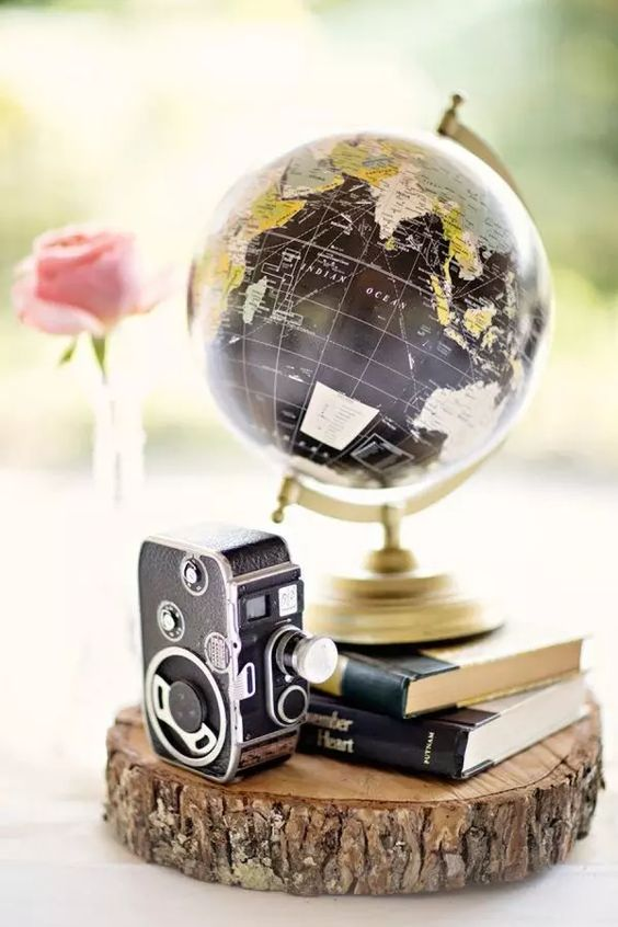 a chic vintage travel-themed wedding centerpiece of a wood slice, a stack of books, a globe and a vintage camera