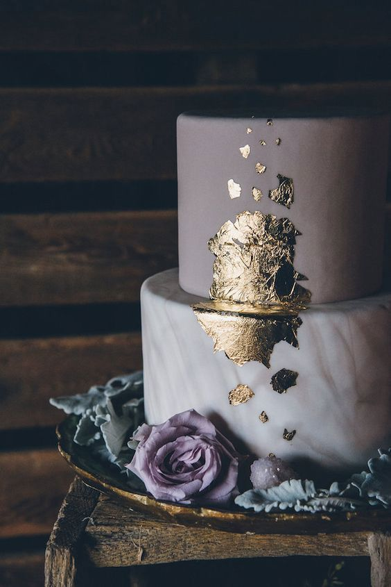a chic wedding cake with a marble and a purple tier plus gold leaf decor and purple blooms