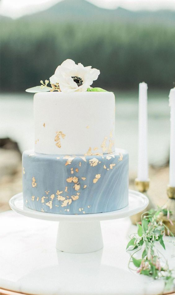 a chic wedding cake with a white and blue marble tier, gold leaf and white anemones on top is a lovely idea