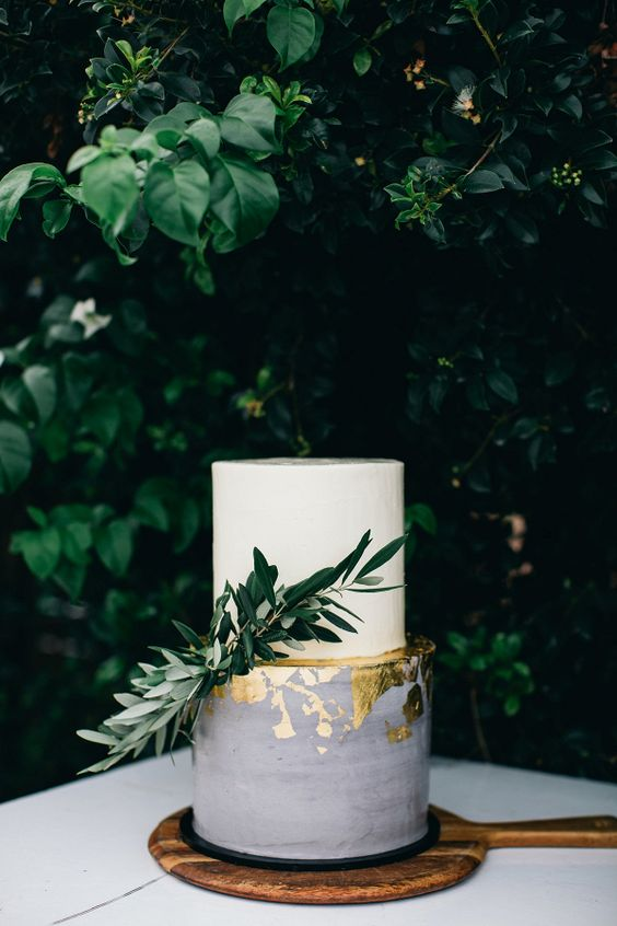 a chic wedding cake with a white and grey tier, gold leaf and greenery looks very elegant and eye catching