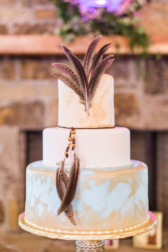 a chic white and blue wedding cake with gold brushstrokes and feathers will fit a boho wedding