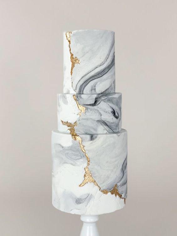 a chic white and grey marble wedding cake with gold leaf and a rough edge is a gorgeous solution for a modern or minimalist wedding