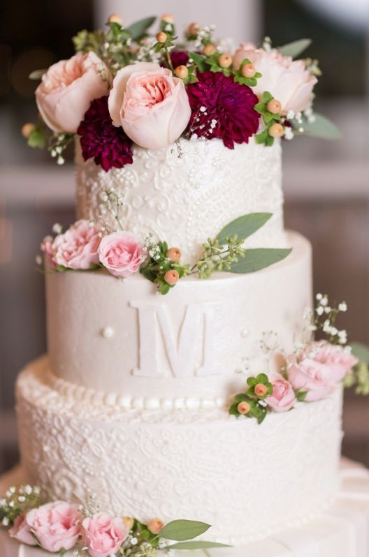 a chic white wedding cake with patterned and a sleek tier, with pink and burgundy blooms and greenery for a spring or summer wedding