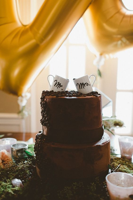 a chocolate wedding cake with coffee beans and coffee mugs on top is a cool idea for a coffee-loving wedding