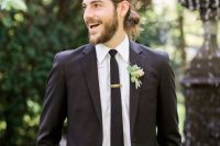 a classic black suit, a black tie and a white shirt for a bold and modern look and a messy man bun that relaxes the look