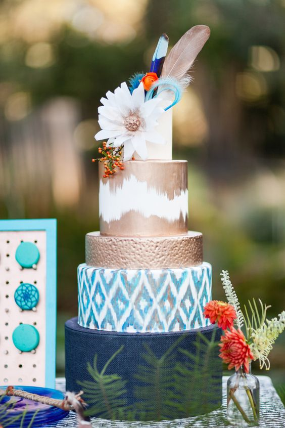 a colorful boho wedding cake with a navy, ikat, copper and white tier, a bloom and feathers