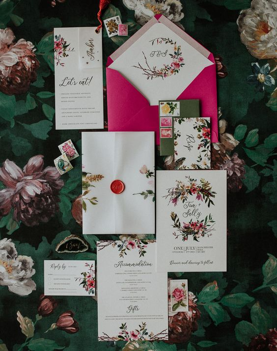 a colorful floral wedding invitation suite with a hot pink envelope, bold floral and greenery patterns adn bright seals