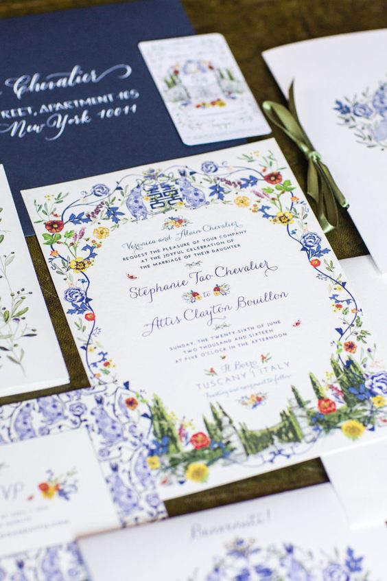 a colorful wedding invitation suite with navy envelopes, colorful floral patterns and greenery and blue calligraphy