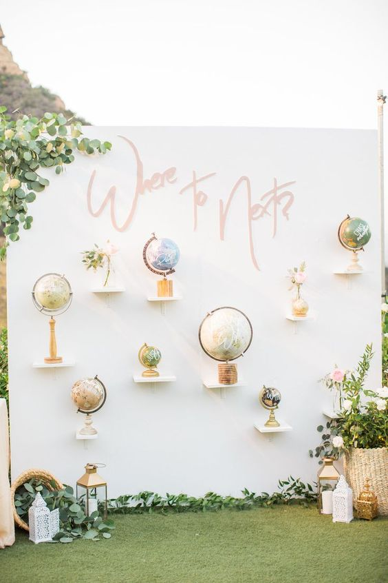 a cool wedding backdrop or photo booth backdrop with various globes and blooms and greenery around