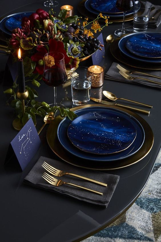 a dark and refined wedding tablescape with blue starry plates, matching cards, gold cutlery, dark blooms and candles for an astronomy wedding