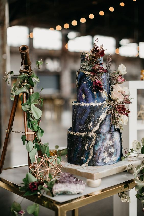 a dark celestial wedding cake done in navy, black and purple, with a gold edge and lush blooms