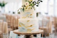 a delicate blue watercolor wedding cake with gold leaf, with white blooms and greenery is a chic idea