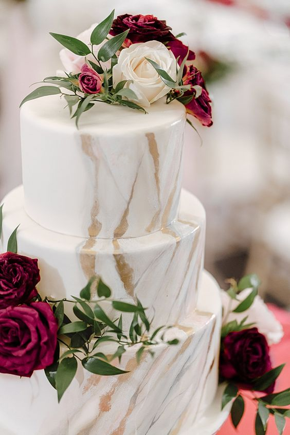 a fabulous white marble wedding cake with white and burgundy blooms and greenery is a gorgeous idea for a modern wedding