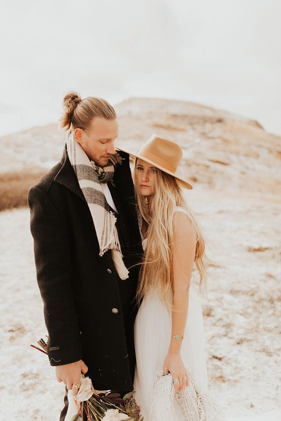 a fall boho groom look with a black coat, a striped scarf and a messy man bun on top to look more relaxed and casual