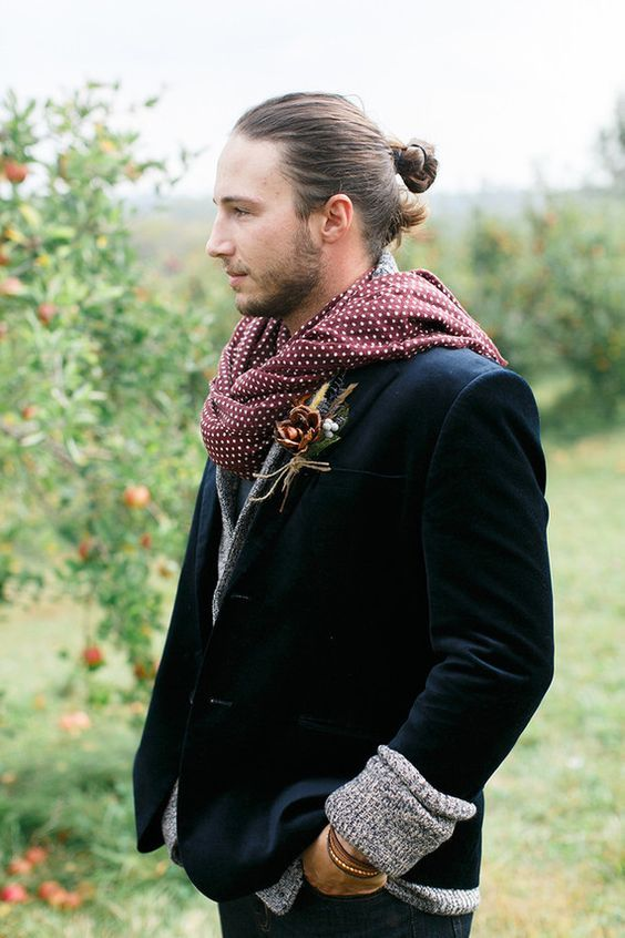 a fall boho groom outfit with a black velvet blazer, a grey cardigan, a polka dot scard and a man bun is wow