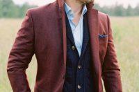 a fall or winter boho groom look with a blue shirt, a navy cardigan, a burgundy blazer, green pants and a braided man bun