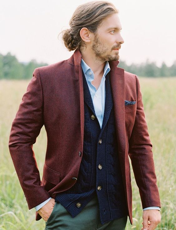 a fall or winter boho groom look with a blue shirt, a navy cardigan, a burgundy blazer, green pants and a braided man bun
