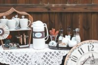 a fall wedding coffee bar with mugs, sweets, tanks and kettles plus a lace tablecloth and a large clock for a vintage wedding