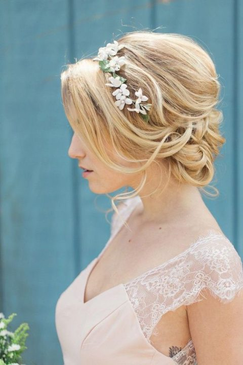 a girlish wavy low updo with a bump and some waves down plus a floral crown looks amazing