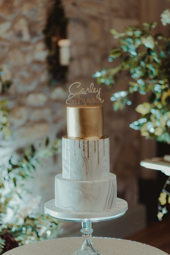 a glam wedding cake with white marble and a gold tier, with drip and a calligraphy topper is amazing