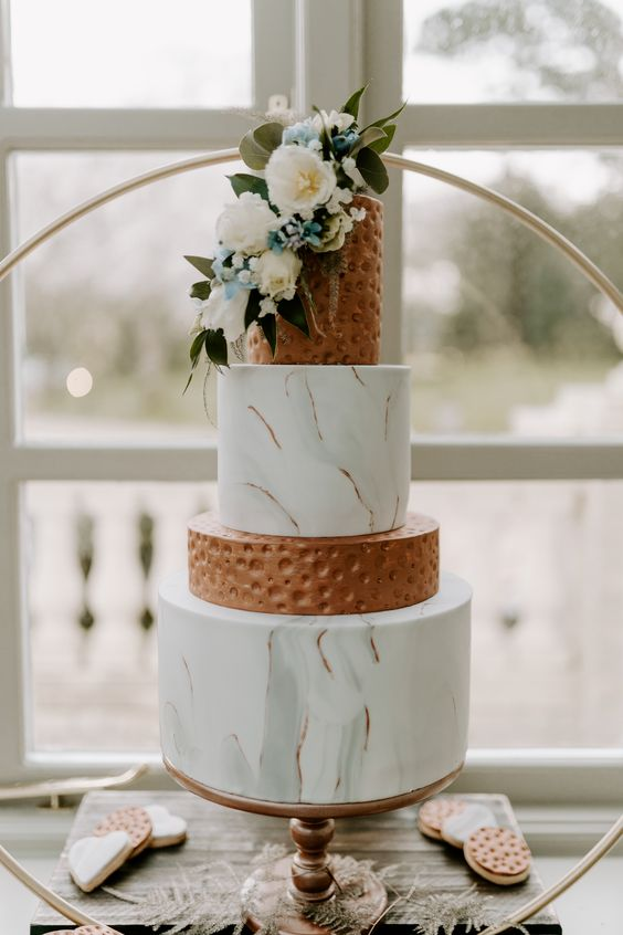 a gorgeous wedding cake with grey marble and copper tiers, with white and blue flowers and greenery for a summer wedding