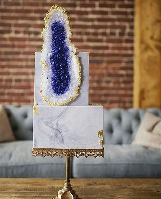 a grey marble wedding cake decorated with gold leaf and a large sugar geode in purple for an elegant wedding