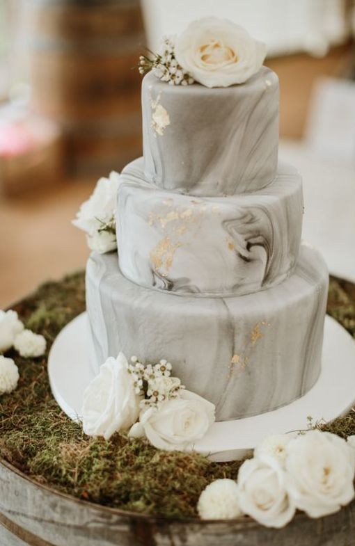 a grey marble wedding cake with gold leaf, white blooms is a lovely and refined solution for a modern wedding