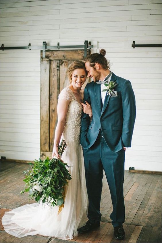 a grey suit, a light grey bow tie, a messy man bun to highlight the rustic style of the groom