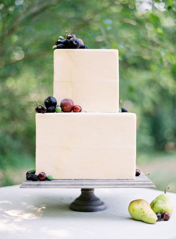 a laconic neutral square wedding cake topped with fresh fruits and berries for a modern wedding