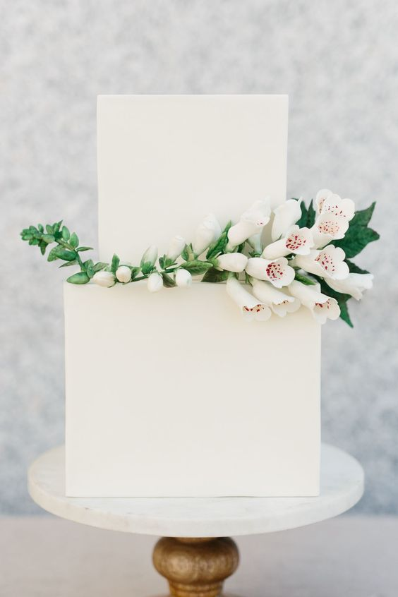 a laconic white square wedding cake decorated with a branch of white blooms is a stylish idea for a minimalist wedding