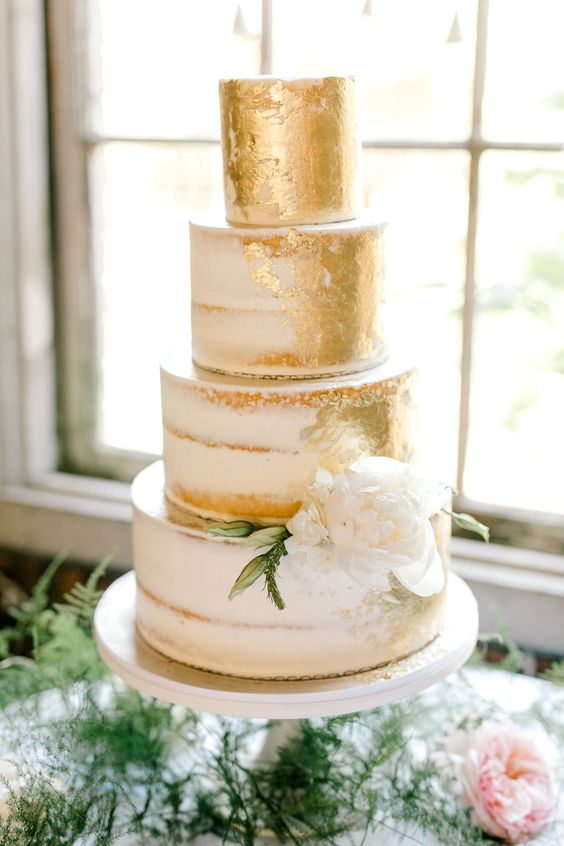 a large naked wedding cake with gold leaf and a single white flower is a super chic and elegant idea