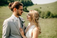 a light grey suit, a white tie and shirt, a beard and a messy man bun to downgrade the formal outfit a little bit