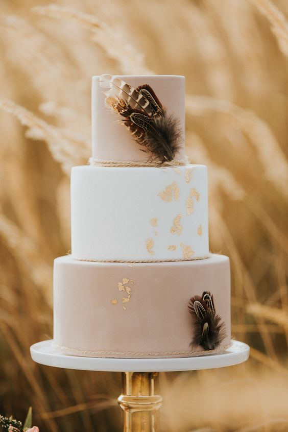 a lovely blush and white wedding cake with rope, feathers and gold leaf is stylish and very romantic
