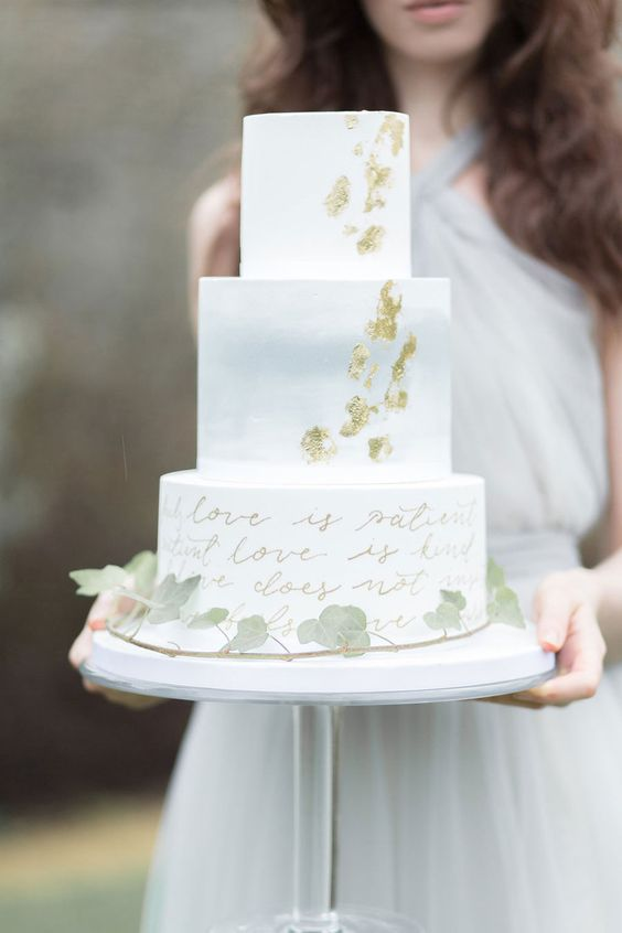 a lovely wedding cake with a white, watercolor blue and calligraphy tier, gold leaf and greenery that covers it