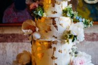 a lush and bold wedding cake with gold leaf, greenery and lots of pink and white blooms looks wow